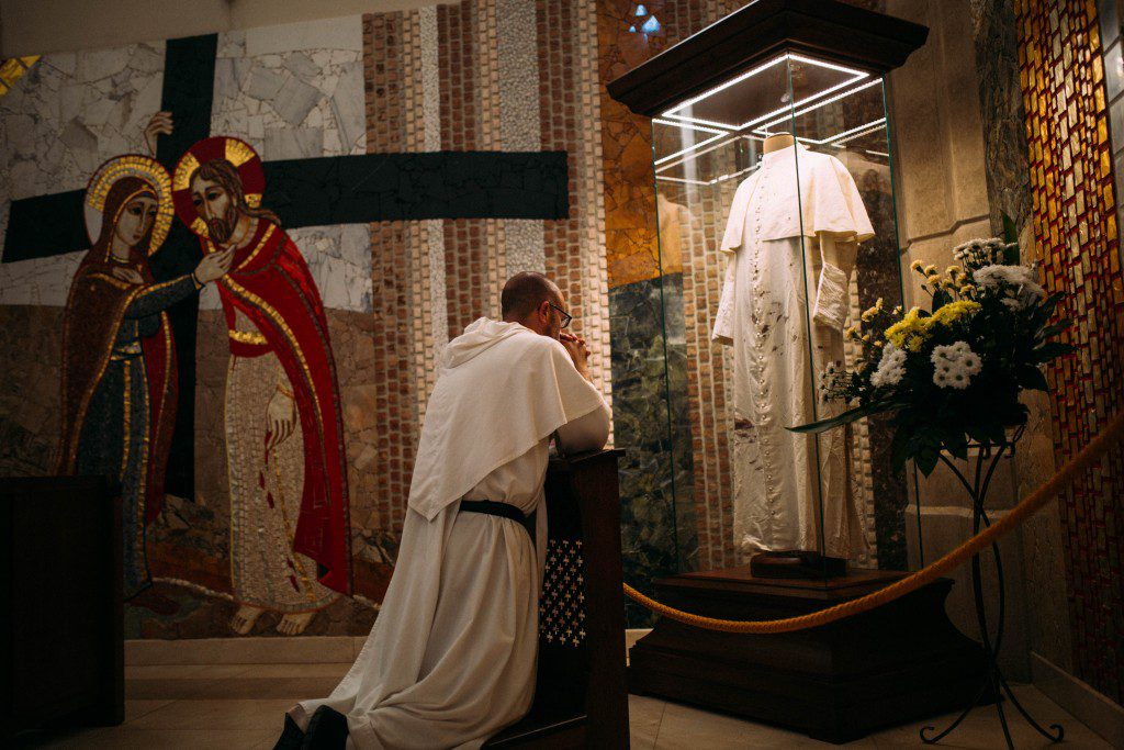 Fr. James Cuddy, O.P. prays in front of the cassock worn by Saint John Paul II when he was shot on the Feast of Our Lady of Fatima; this photo was taken at the Saint John Paul II Sanctuary in Krakow, Poland.
